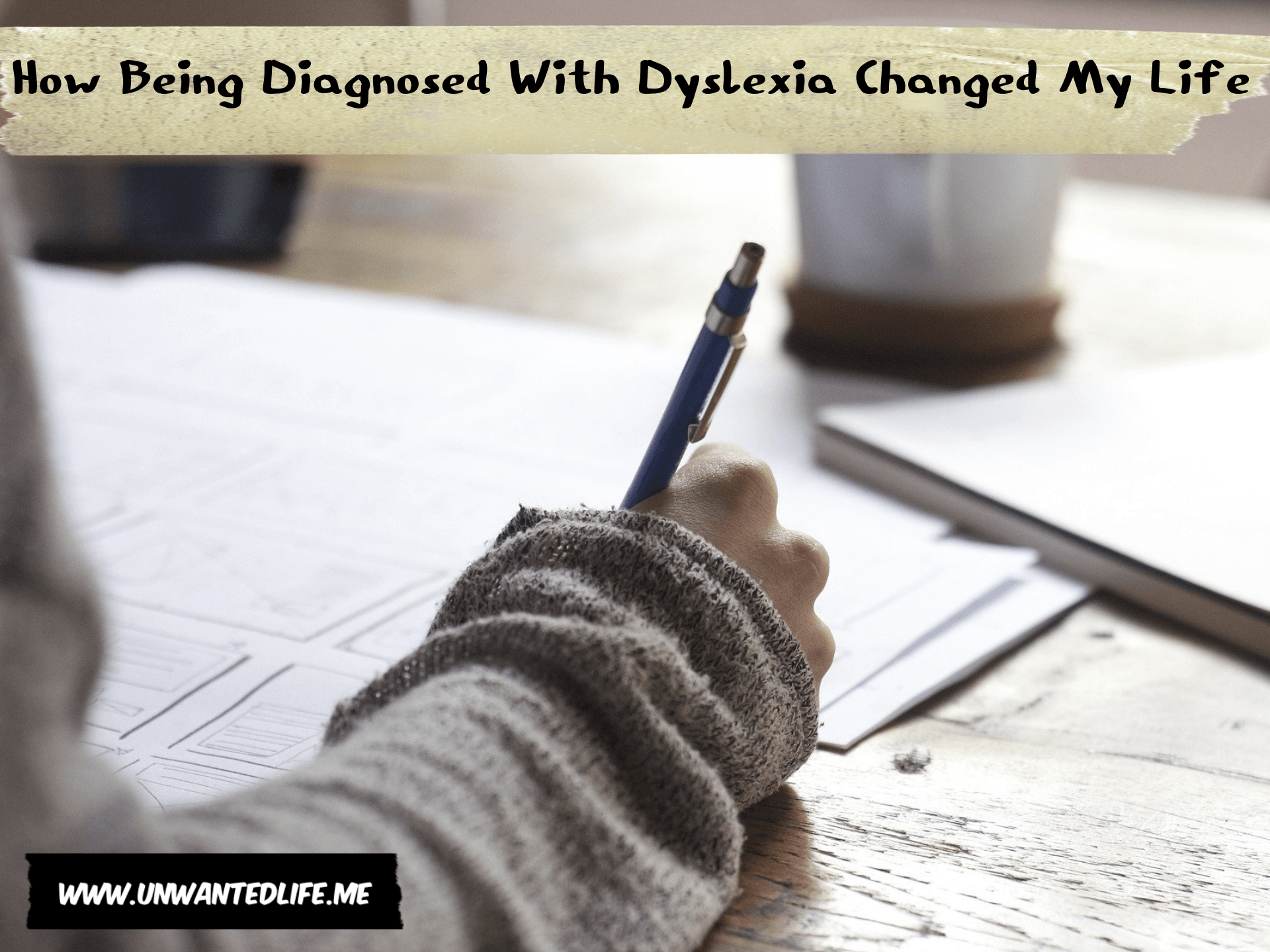 A white person sitting at a table writing to represent the topic of the article - How Being Diagnosed With Dyslexia Changed My Life