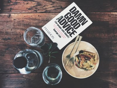 A book on a dinning room table that has the title, Damn Good Advice, to reflect that content of this article to provide advice from Twitter for supporting someone with Mental Health Problems