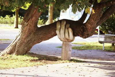 A photo of a wooden carved hand supporting a sideways growing tree truck to represent Twitter's Advice For Supporting Someone With Mental Health Problems