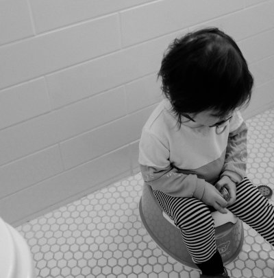 A black and white photo of a kid sitting on a potty in a bathroom
