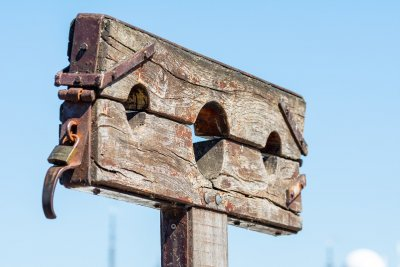An image of a pillory or stocks made of wood, which is a device made with holes for securing the head and hands of a person so they can be publicly humiliated. This image reflects society for pill shaming