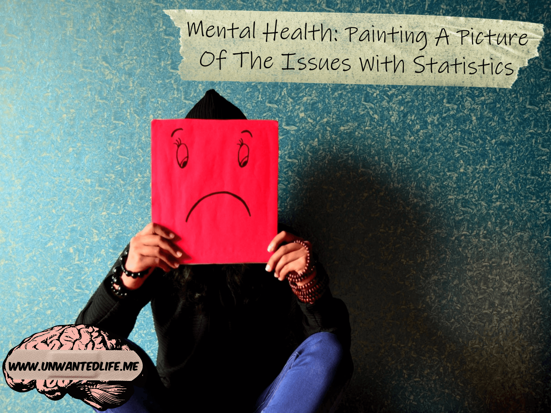 A photo of a person sitting down against the wall hiding their face behind a simple drawing of a sad face with the article title - Mental Health: Painting A Picture Of The Issues With Statistics - across the top of the photo