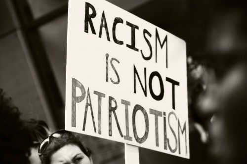 """A photo of a protest placard that says """"racism isn't patriotism"""" to represent the topic of the article - Brexit And Hate Crimes: Do You Feel Safe?"""