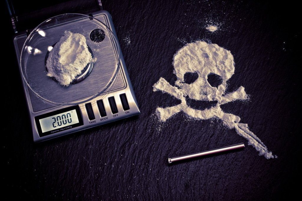 A picture of a white substance on set of digital scales with a skull and cross bones made out of the white power next to it, with a snorting paraphernalia next to it to represent the drug abuse described in this article