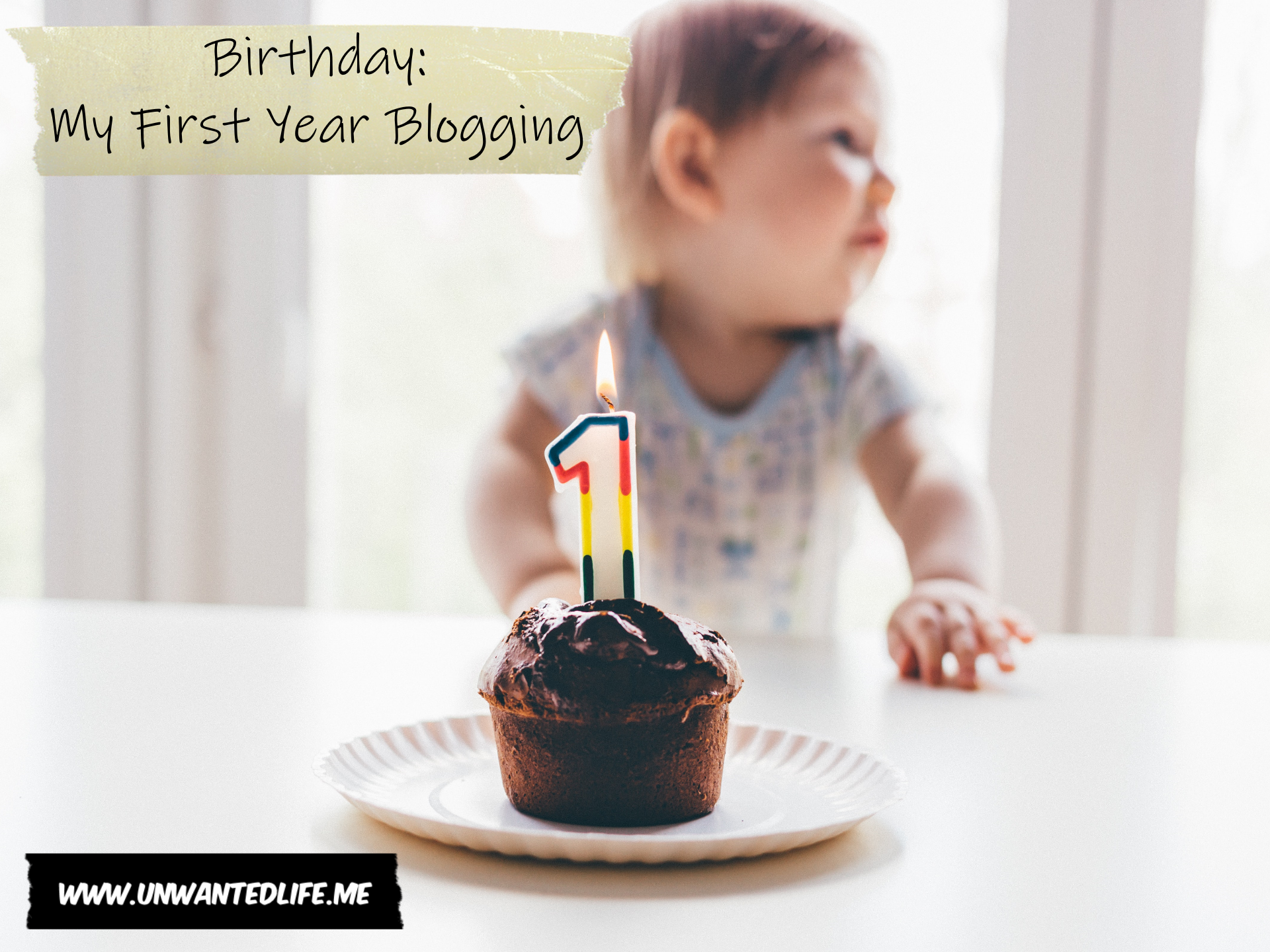 A photo of a baby and a small birthday cake with a number one candle lit on the cake to represent - Birthday: My First Year Blogging