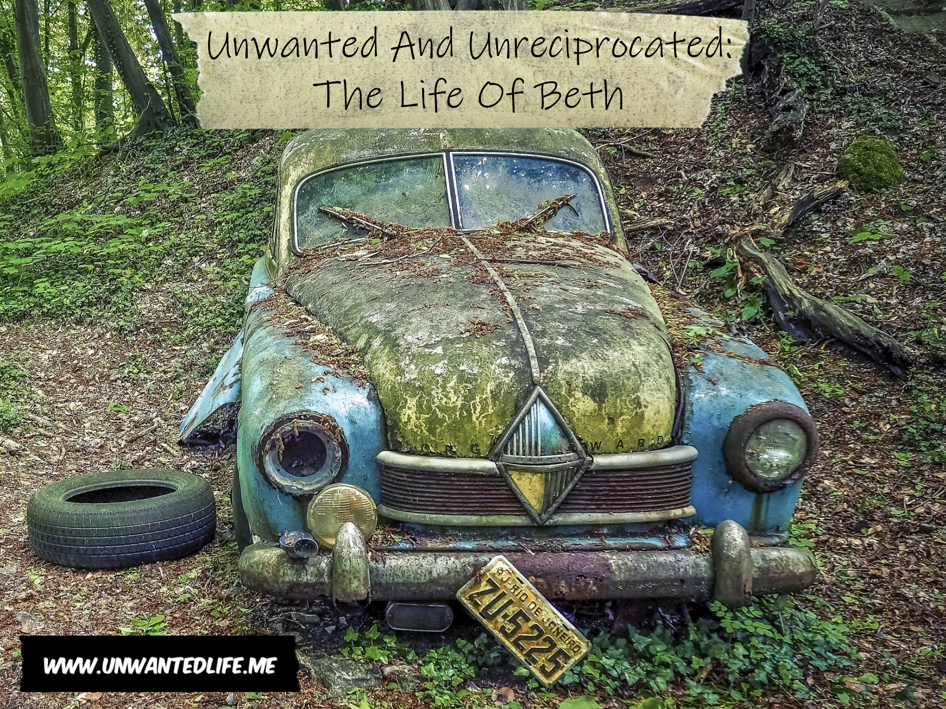 A very old, rusted, and unwanted car abandoned in the woods
