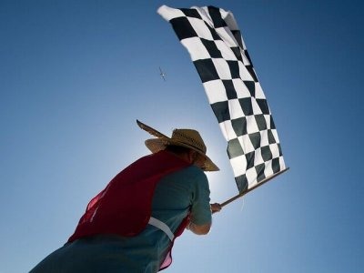 A South America man waving the chequered flag to represent the topic of the article - Race Across The World, With Your Mum