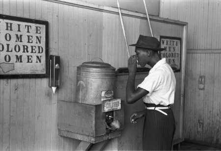 A black and white photo of a black man drinking from the water meant for coloured people segregation America (USA) to represent the topic of the article -  Discrimination: Black Lives Matter And LGBTQ+