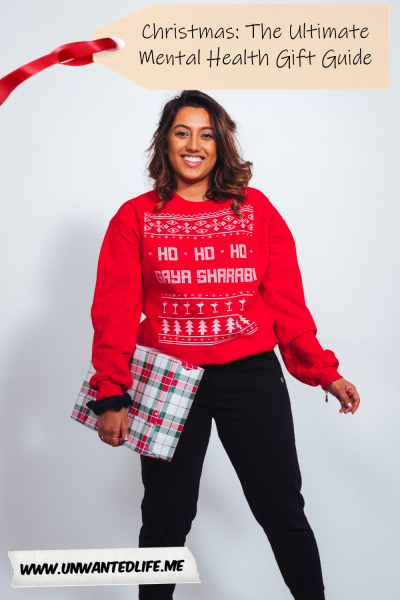 A woman of Indian decent in a Christmas jumper holding a present to represent - Christmas: The Ultimate Mental Health Gift Guide