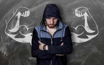 An image of a skinny white male in a hoodie standing in front of a chalkboard which has muscular arms drawn on it to represent muscle dysmorphia