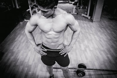 A photo in black and white of a muscular white man posing in a gym to represent the disparity in male eating disorder care and is prevalent in the body building community to represent the article title - Why Is There A Disparity In Male Eating Disorder Care?