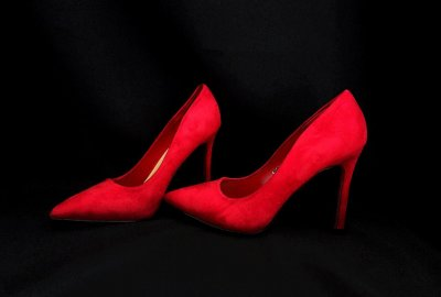 A pair of red Stilettos surrounded by back velvet
