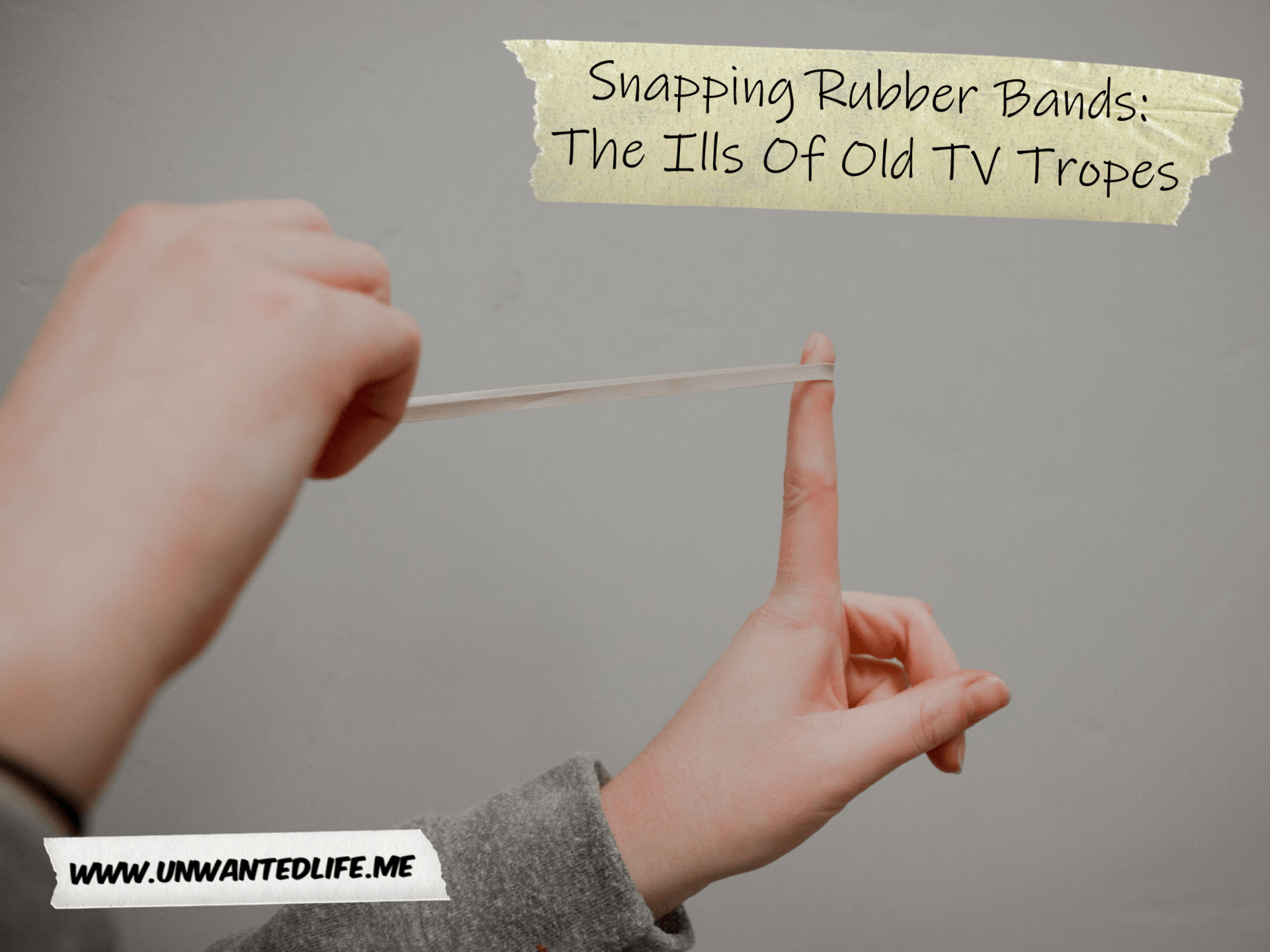 A photo of a young persons hand pulling back a rubber band ready to shoot it off with the article title - Snapping Rubber Bands: The Ills Of Old TV Tropes - in the top right corner of the photo