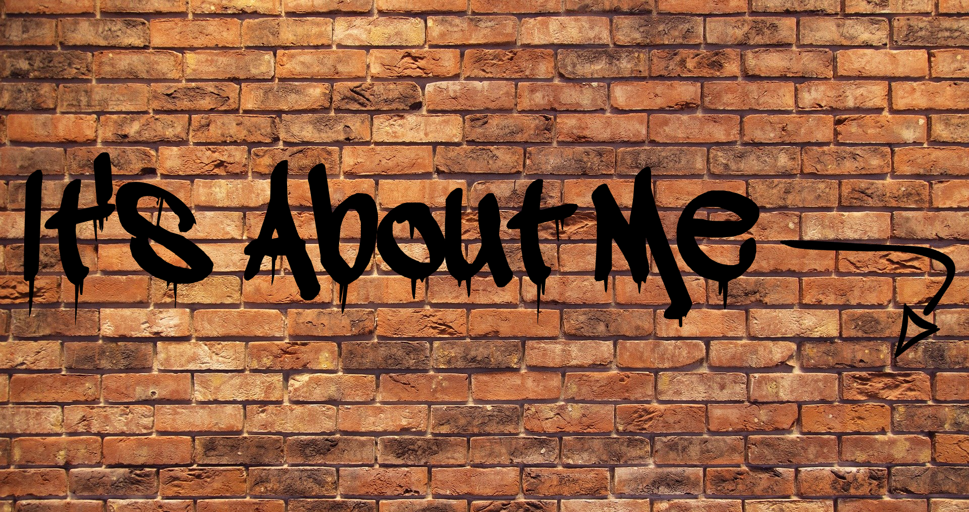 "A picture of a wall with the words ""It's About Me"" spray painted on it with an arrow pointing downwards to reflect the topic of the page - About Me"