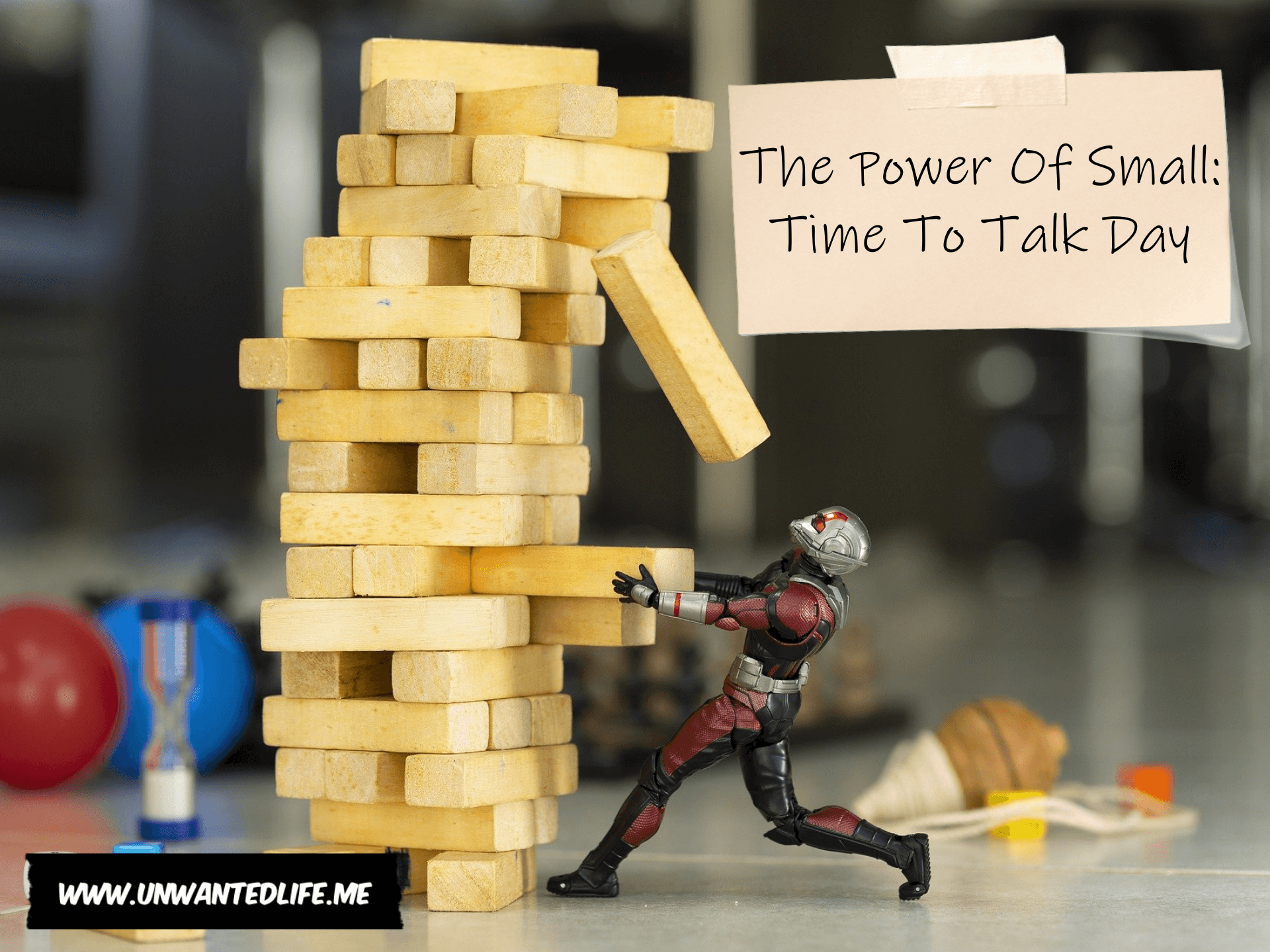 A photo of a Marvel's and Disney's Ant Man action figure pulling a Jenga piece with the title of the article - The Power Of Small: Time To Talk Day - in the top right corner of the image