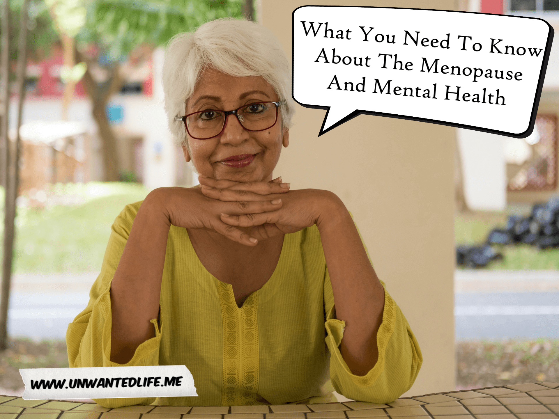 A photo of a mature woman of Indian decent sitting at a table with her hands resting on her hands with to represent the topic of the article - What You Need To Know About The Menopause And Mental Health