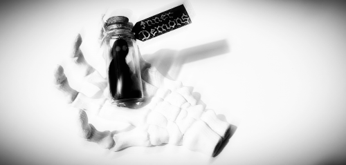 A photo of a literally representation of your Inner Demons in a small glass bottle which is resting on a skeleton hand