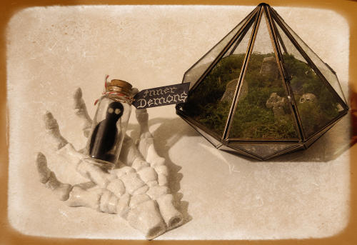 A photo of a literally representation of your Inner Demons in a small glass bottle which is resting on a skeleton hand next to a graveyard terrarium