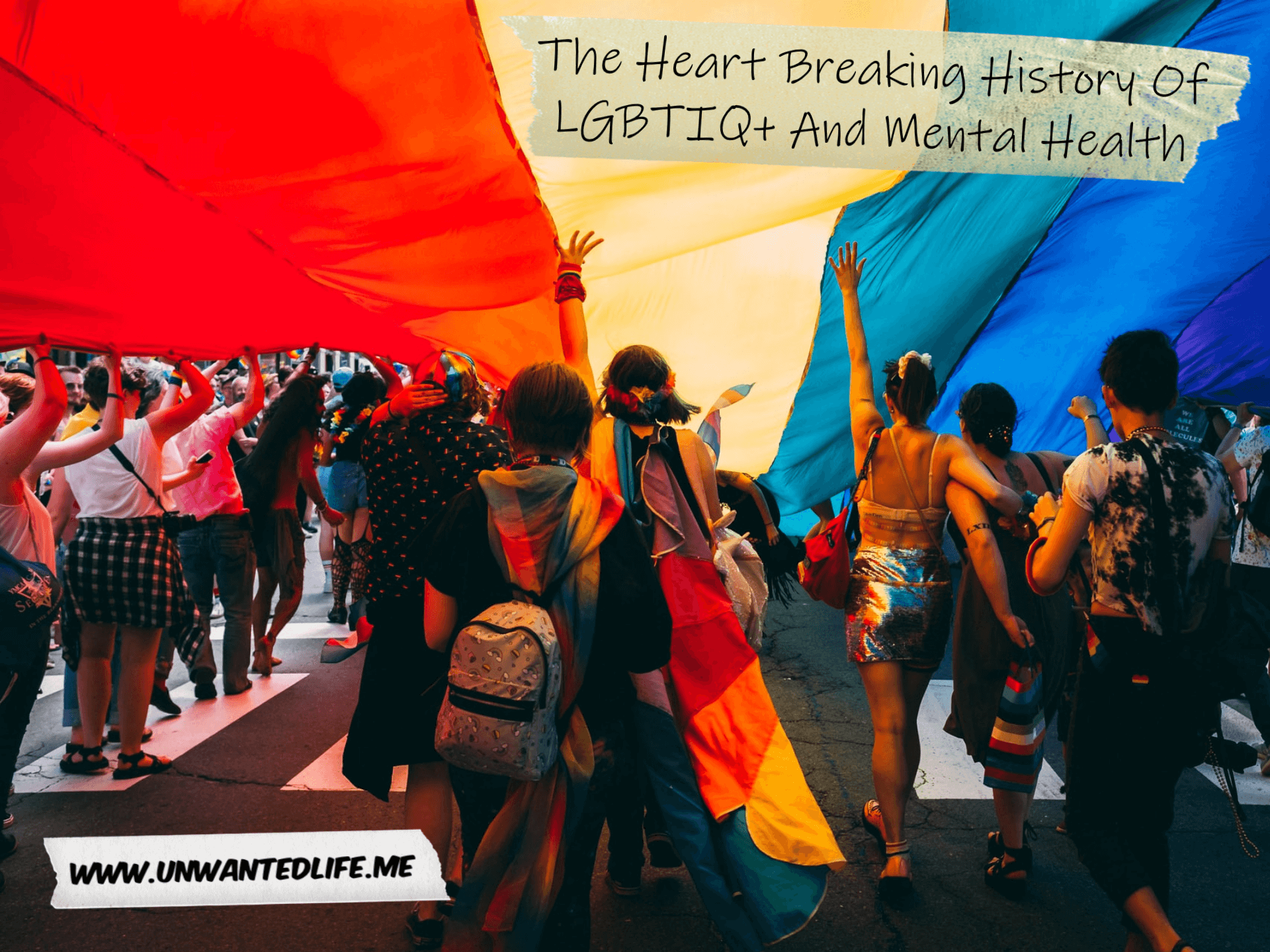 A photo of a pride event with people walking under a giant LGBT+ flag to represent the topic of the article - The Heart Breaking History Of LGBTIQ+ And Mental Health