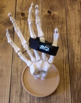A photo of a skeleton hand displaying a Fitbit Charge 4 to represent the topic of the article - Health Data: A Triple Review Of Health And Medical Devices
